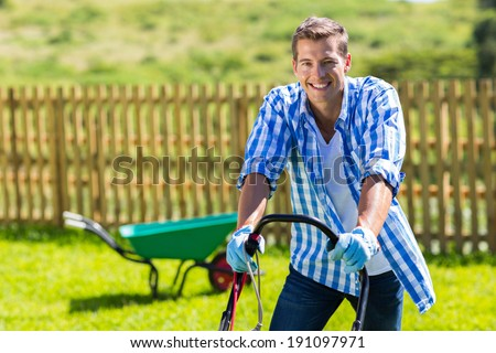 happy man mowing lawn at home garden - stock photo