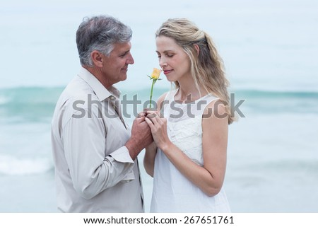 Happy man offering flower to his girlfriend at the beach - stock photo