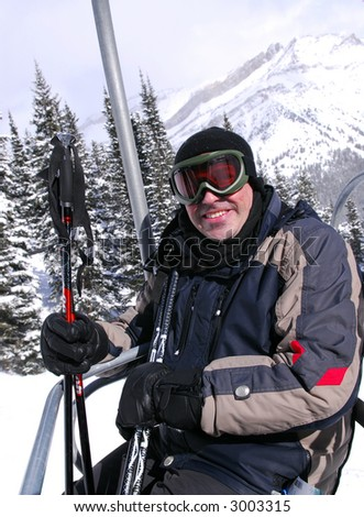 Happy man on a chairlift at downhill ski resort - stock photo