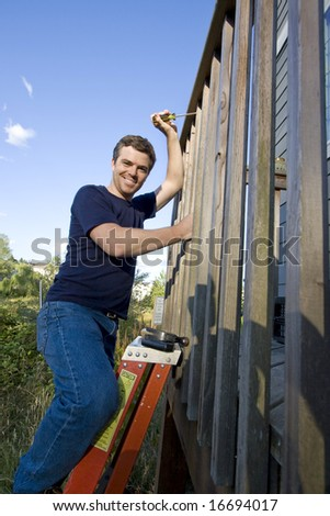Happy man on a ladder repairing siding of a house with a screwdriver. Vertically framed photo. - stock photo