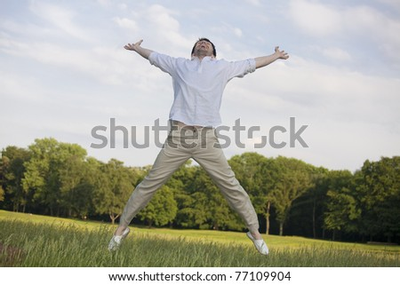 happy man on meadow jumping in the air - stock photo