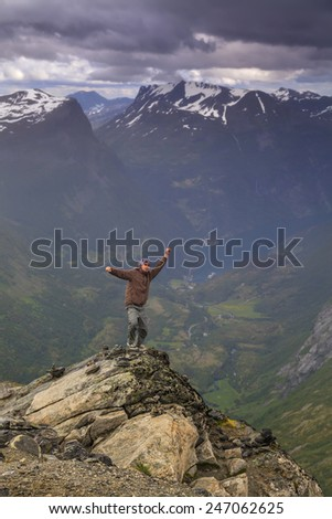 Happy man on the top of a high mountain - stock photo