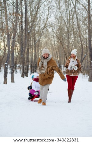 Happy man pulling sledge with kids in winter park - stock photo