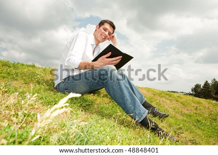happy man reading a book sitting on green grass - stock photo
