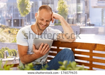 Happy man reading e-book outdoors, smiling, using earbuds. - stock photo