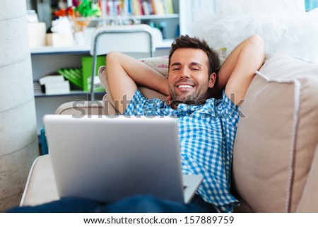 Happy man relaxing with laptop on couch