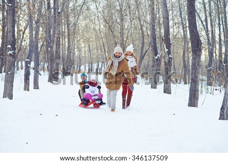 Happy man riding kids on sledge in winter park - stock photo
