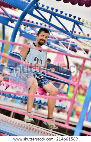 Happy man riding on ferris wheel at amusement park - stock photo