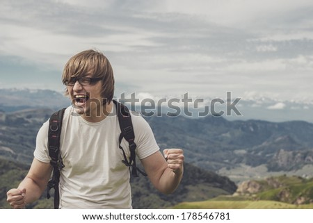 happy man shouting at the mountain top - stock photo