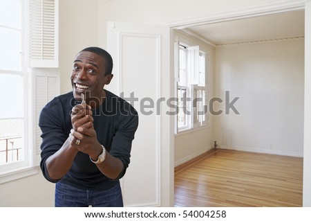 Happy man showing off the key to his new home - stock photo