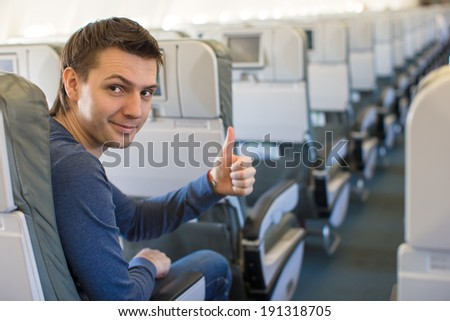 Happy man showing thumbs up inside the aircraft - stock photo