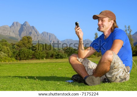 Happy man sits on grass and reads/sends sms - and misty mountains are background. Shot in Stellenbosch, South Africa.