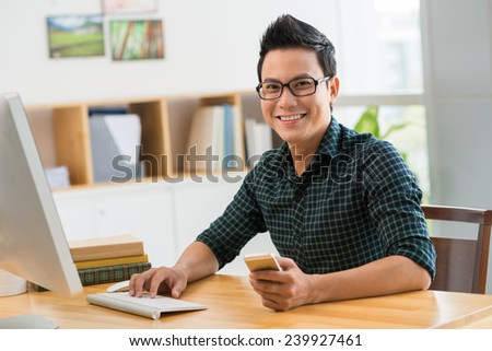 Happy man sitting at his workplace looking at the camera - stock photo
