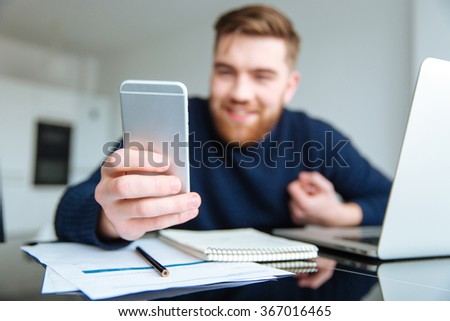 Happy man sitting at the table and using smartphone. Focus on smartphone - stock photo