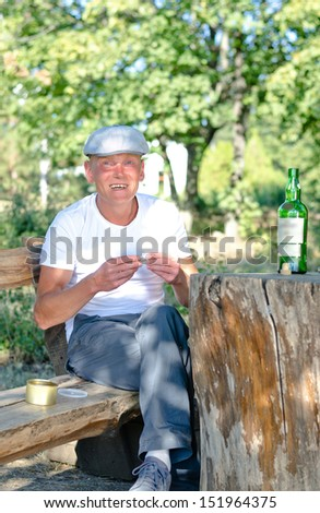 Happy man sitting on an old rustic wooden bench in woodland smoking rolled cigarettes and drinking directly from a bottle of spirits