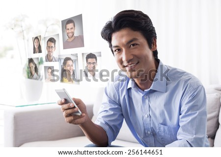 Happy man sitting on couch texting on phone against profile pictures - stock photo