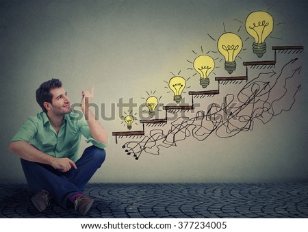 Happy man sitting on floor in his office pointing at business education success, promotion, company growth isolated gray wall texture background. Handsome guy looking up at growing up light bulbs - stock photo