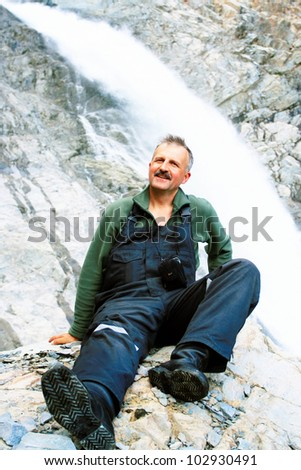 Happy man sitting on the cliff