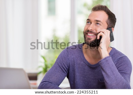 Happy man smiling as he chats on his smartphone looking up into the air as he listens to the conversation, indoors at home with a window backdrop - stock photo