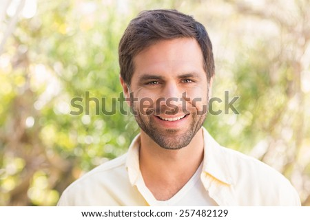Happy man smiling at camera on a sunny day - stock photo