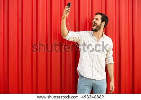 happy man smiling at his cellphone on red background with free space