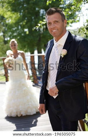 Happy man smiling on wedding-day, bride at background. - stock photo