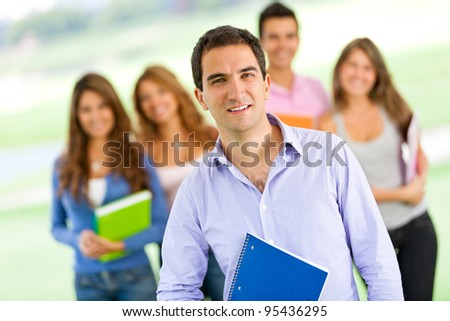 Happy man smiling with a group of students - stock photo