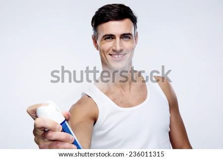 Happy man spraying deodorant over gray background - stock photo