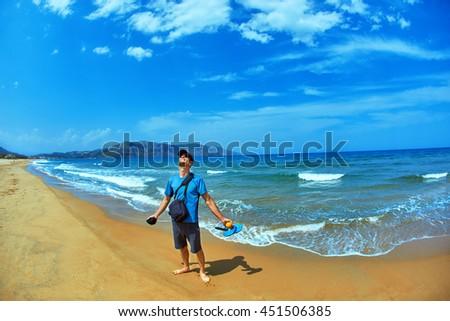 happy man stands on the empty sunny beach, Crete, Greece - stock photo