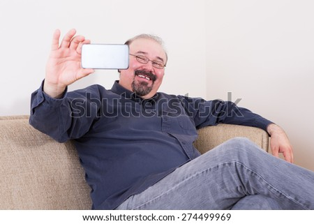 Happy man taking a selfie for his friends on the social media on his smartphone posing on a couch at home looking at the camera with a beaming smile - stock photo