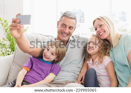 Happy man taking selfie with family on sofa at home - stock photo