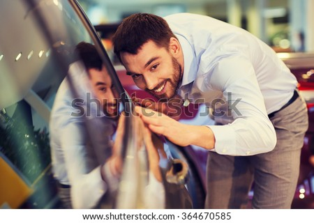 happy man touching car in auto show or salon - stock photo