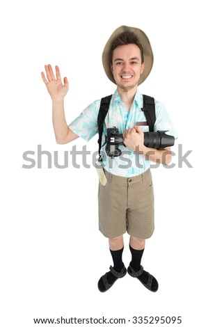 Happy man tourist in blue shirt, brown shorts and hat with backpack on his shoulders holding dslr camera. Traveler smiling and greeting someone by hand. Isolated on white background.