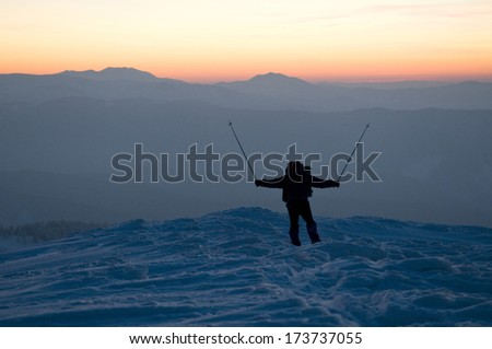 Happy man (tourist) is situated on the top of mountain covered with snow. Sunset and outlines of the mountains are in the background. - stock photo