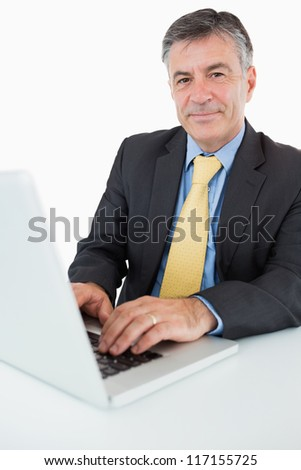 Happy man typing on his laptop at his desk - stock photo