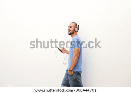 Happy man walking with mobile phone listening to music on headphones - stock photo