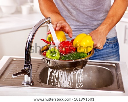 Happy man washing fruit at kitchen. - stock photo