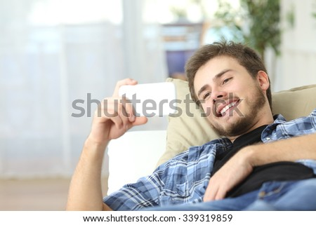 Happy man watching movies in a smart phone lying on a couch at home - stock photo