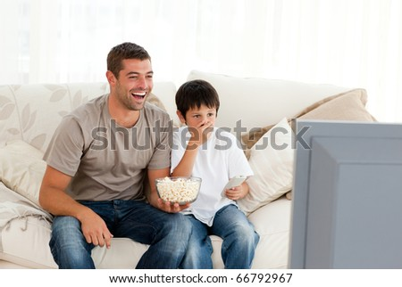 Happy man watching television with his son sitting on the sofa at home - stock photo