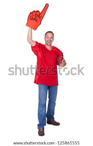 Happy Man Wearing Foam Finger And Holding Rugby Ball On White Background - stock photo