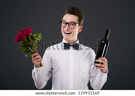 Happy man with a bouquet of roses and wine - stock photo