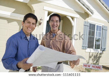 Happy man with architect holding blueprint discussing new house design - stock photo