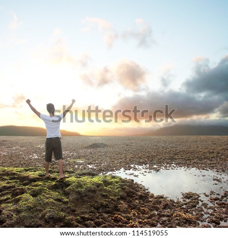 happy man with arms raised on beach - stock photo