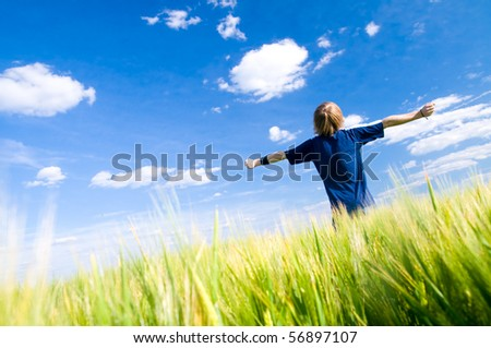 Happy man with arms up on summer field - stock photo