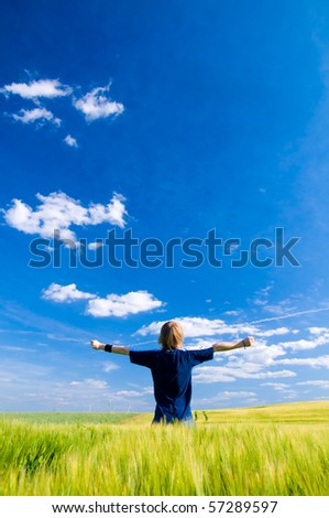 Happy man with arms up on summer landscape - stock photo