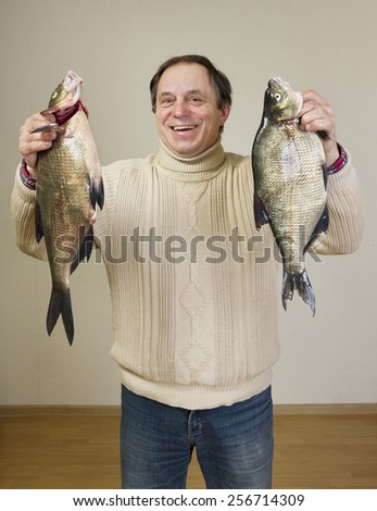 Happy man with big fishes. - stock photo