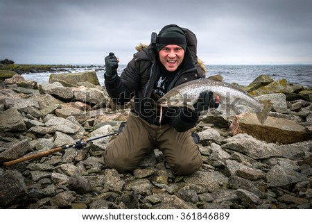 Happy man with big sea trout trophy - stock photo