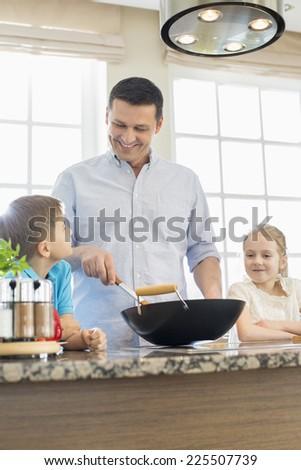 Happy man with children preparing food in kitchen - stock photo