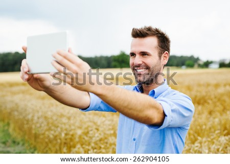 Happy man with digital tablet standing in field - stock photo