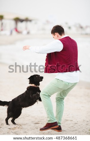 Happy man with dog on the beach